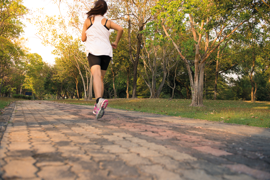 Young woman running in wood, training and exercising for trail r
