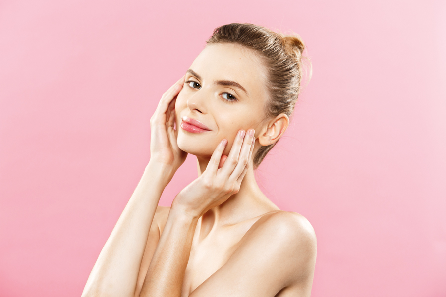 Beauty skin Concept - Beautiful Young Caucasian Woman with Clean Fresh Skin look away with pink studio background. Girl beauty face care. Facial treatment. Cosmetology , beauty and spa.
