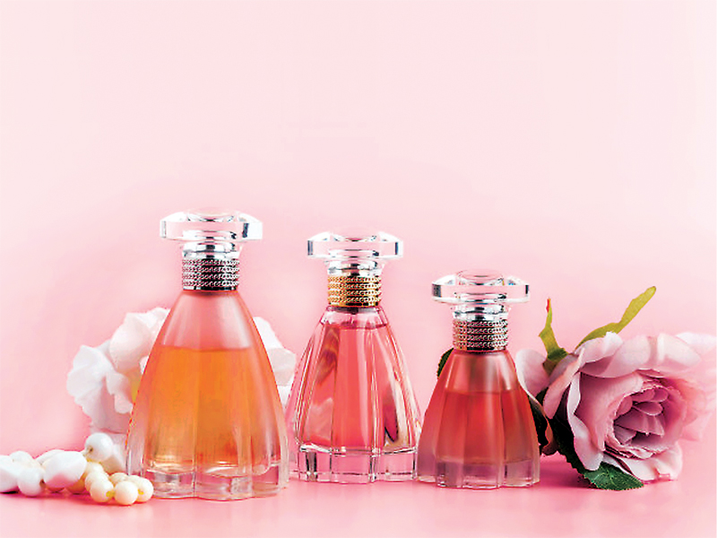 perfume-bottle-with-roses-pink-fabric_127657-878